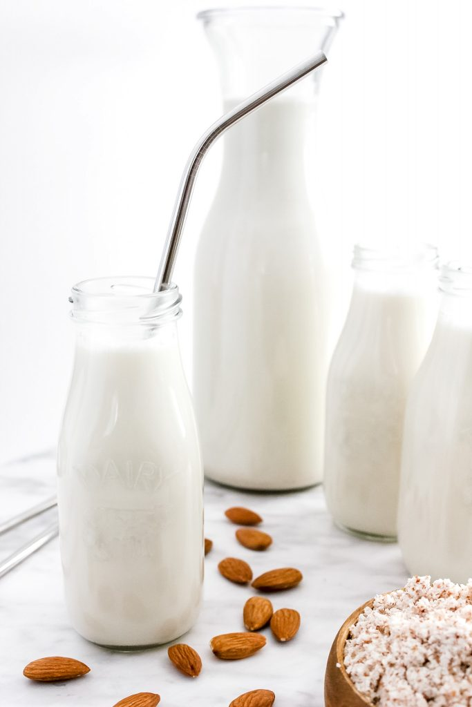 How to Make the BEST Almond Milk (Dairy-Free & Vegan)_Featured Image_in Small Glass Jugs