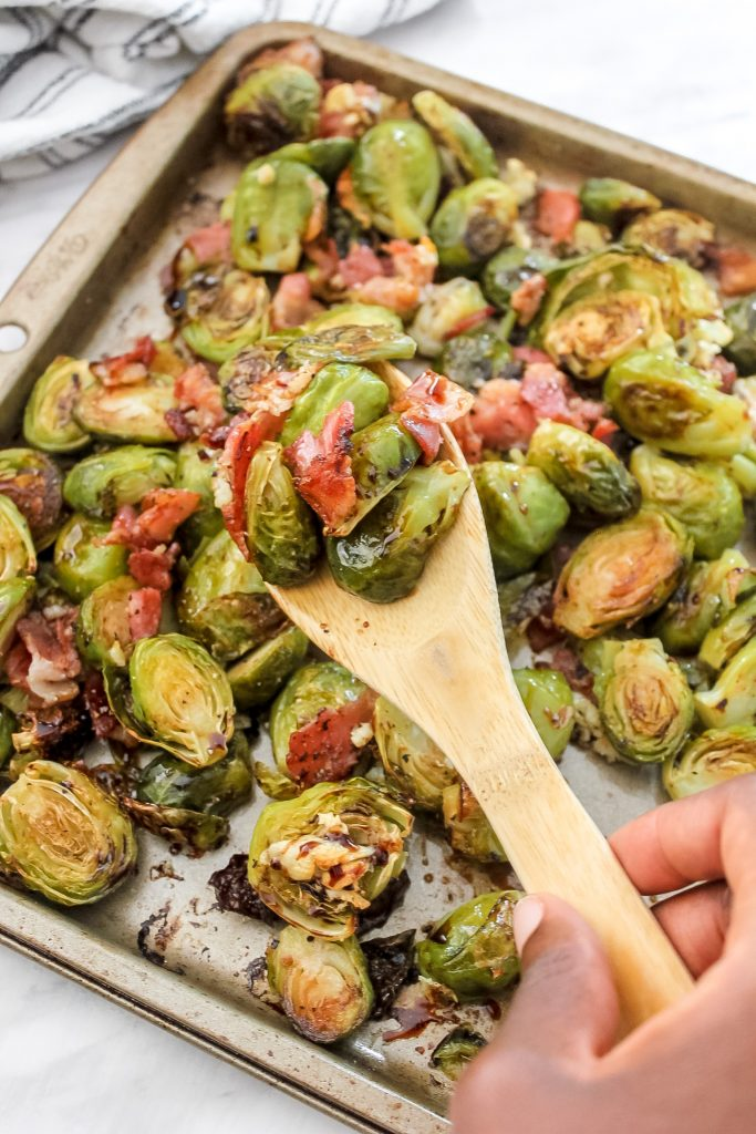 brussels sprouts and bacon on wooden spoon with sheet pan of more brussels and bacon in back