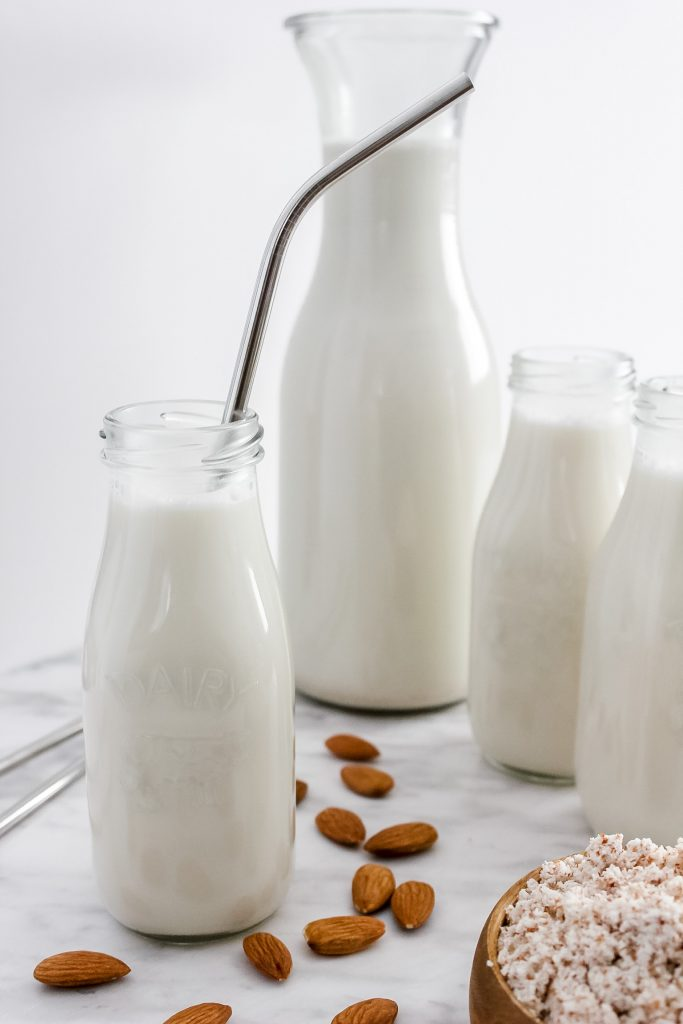 homemade almond milk in small glass jugs