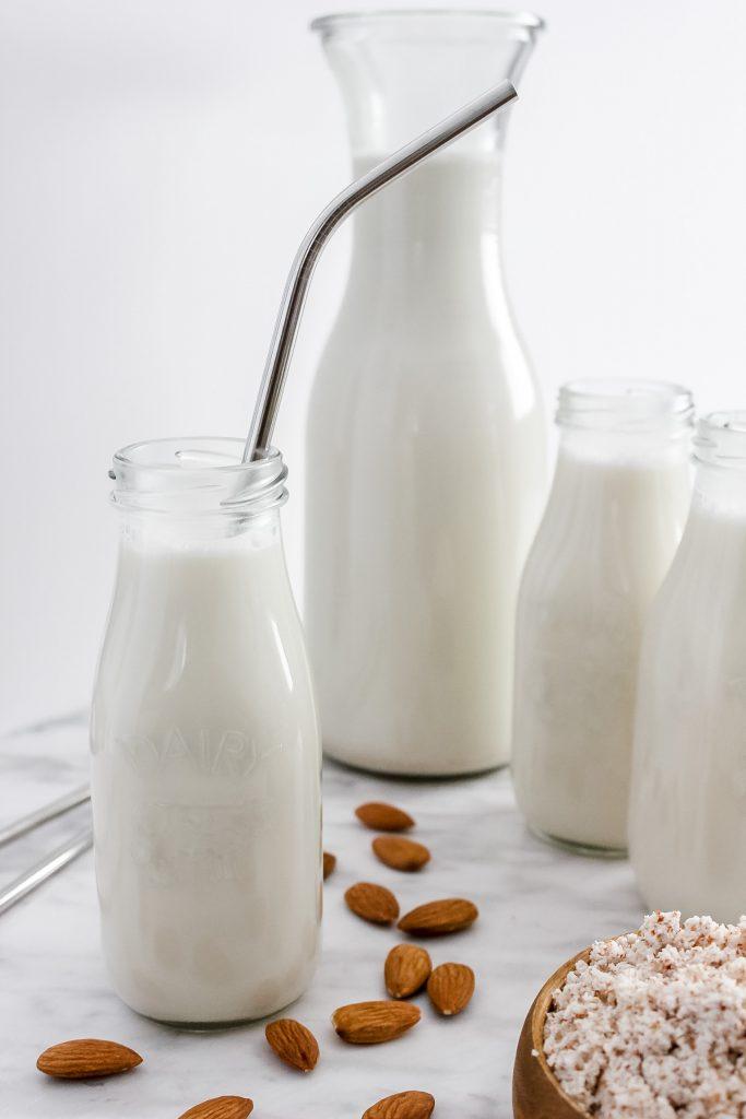 homemade almond milk in small glass jugs