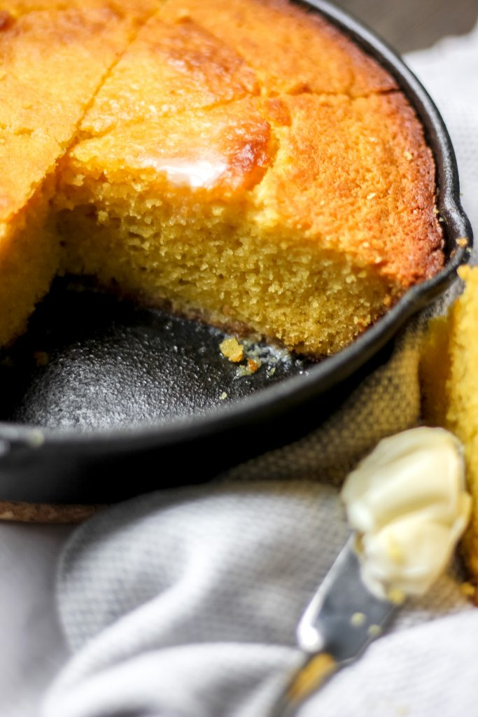 Cornbread in Skillet Sliced with Butter on top