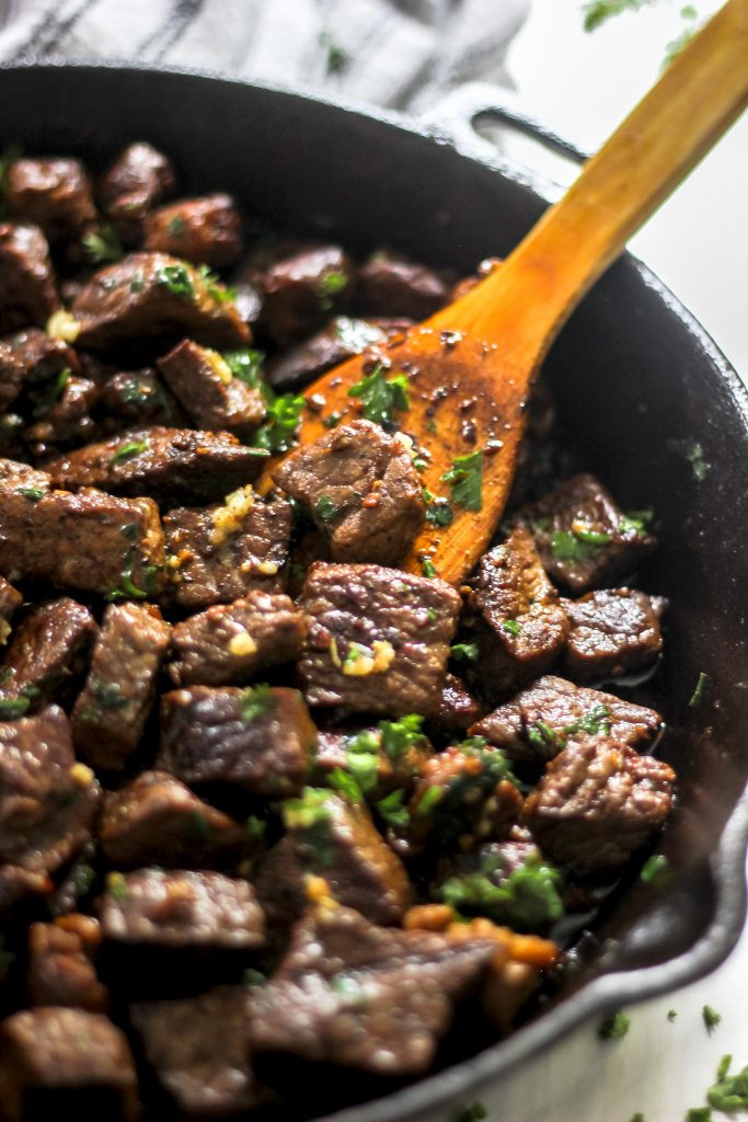 Easy Garlic Butter Steak Bites in Skillet with Wooden Spoon