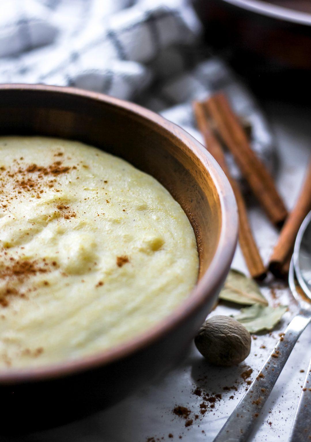 Jamaican Cornmeal Porridge in brown wooden bowl with spoons