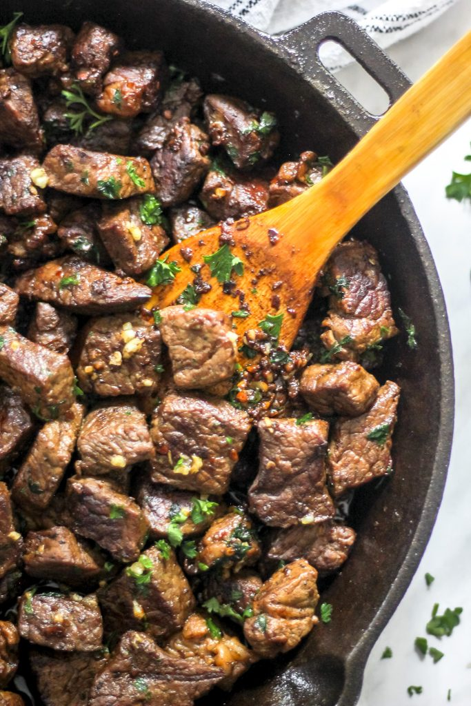 Easy Garlic Butter Steak Bites in Skillet with Wooden Spoon Overhead