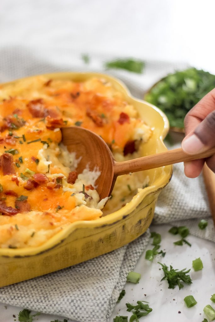 wooden spoon scooping out loaded mash potatoes in yellow casserole dish