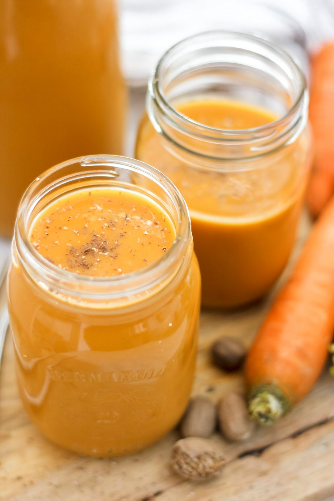 carrot juice in 2 mason jars and a pitcher