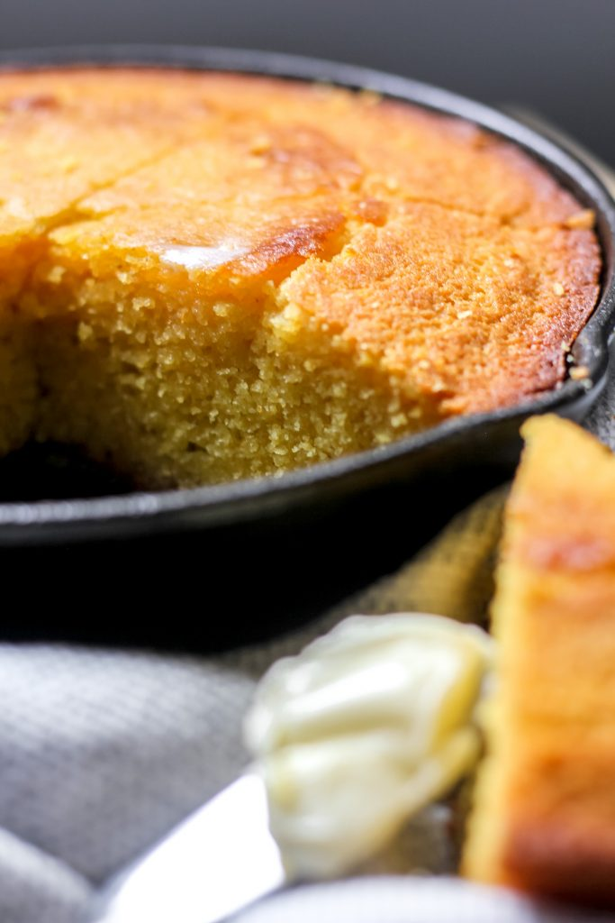 Sweet Cornbread in Cast Iron Skillet with butter on knife and piece on plate