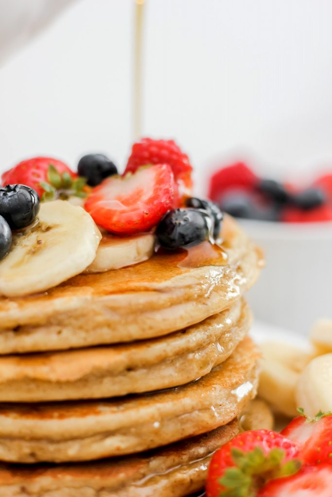 Gluten Free Banana Oat Protein Pancakes stack of 4 with fruit and syrup on top