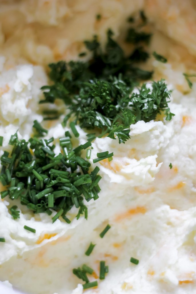 chives, parsley, and green onion on mashed potatoes in pot