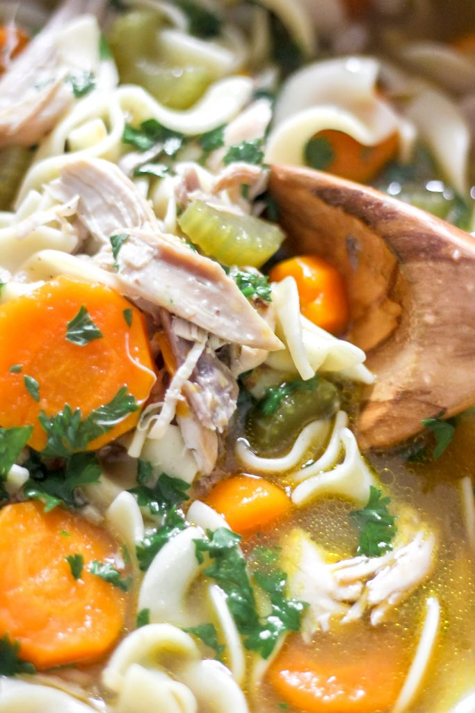 Up Close Classic Homestyle Chicken Noodle Soup in Wooden Spoon