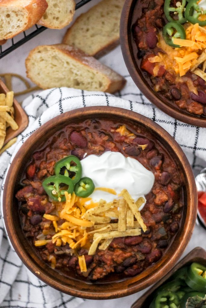 Chili in Wooden Bowls with Sour Cream, Cheddar Cheese, Jalapenos and Tortilla Strips