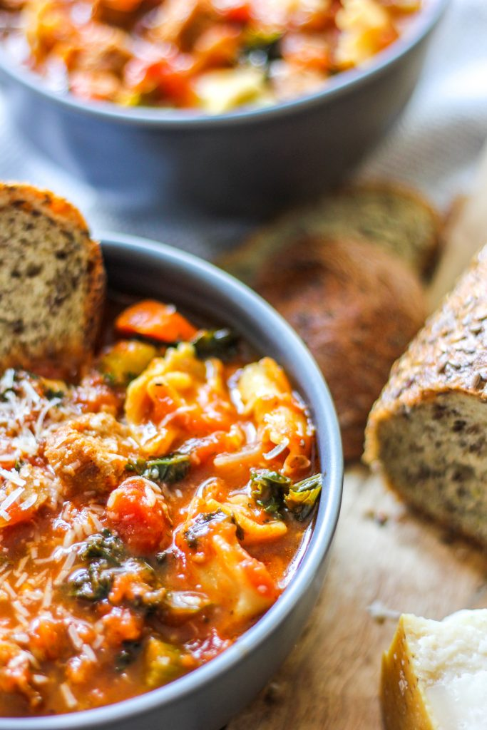 Healthy Hearty Italian Sausage Tortellini Soup in Grey Bowl with Parmesan Cheese and Rustic Bread