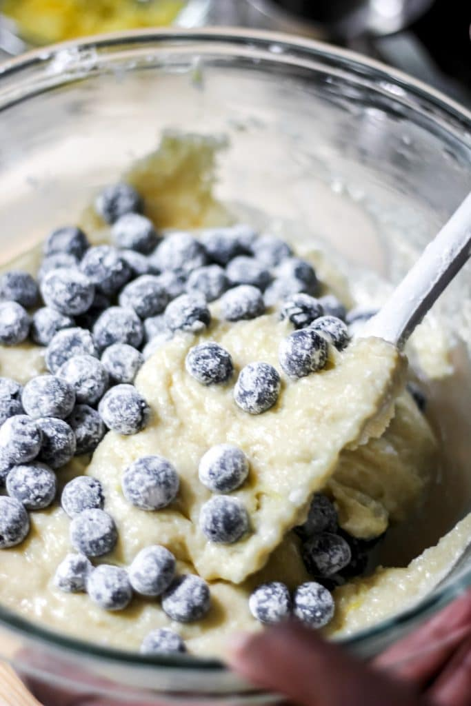 Blueberries tossed in flour placed in Batter