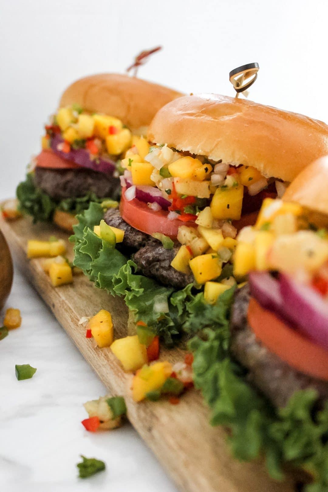 3 Jerk Burgers with Pineapple Mango Salsa on Wooden Board